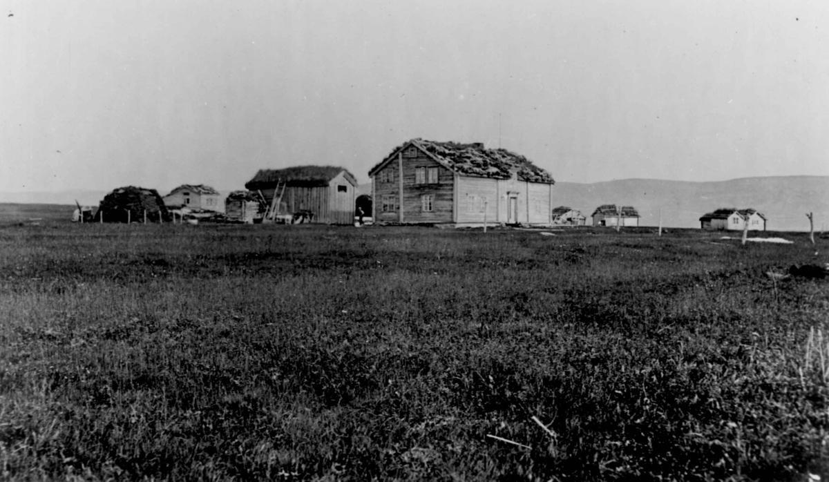 Gårdsanlegg i Finnmark. Laftede bolighus og uthus med torvtak.