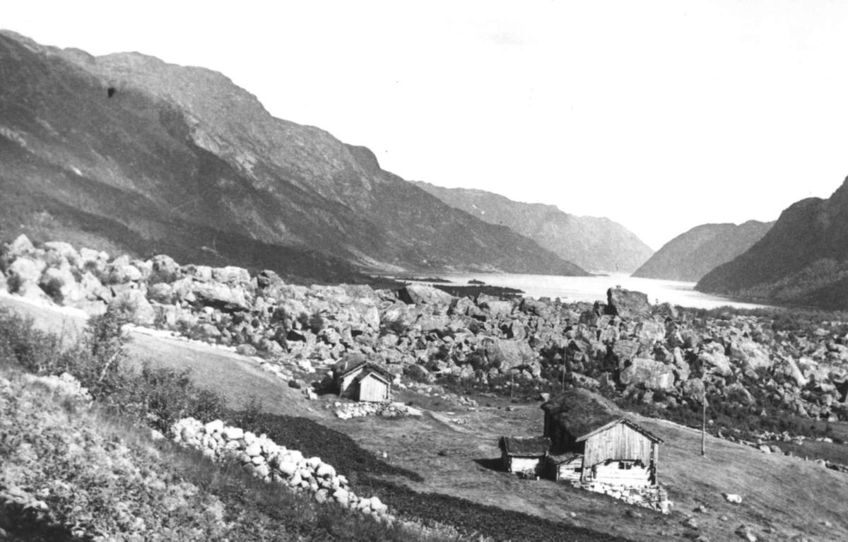 Landskap med fjell og vann. i forgrunnen to bygninger med torvtak. Ukjent sted 1935.