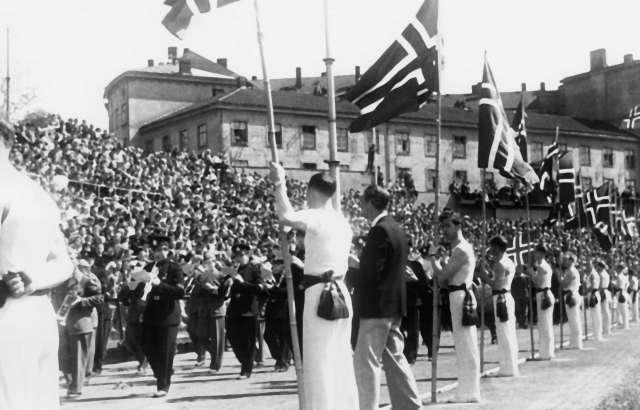Fra Oslo under fredsdagene i 1945. Idrettens Dag på Bislett Stadion 3.juni.Idrettsmenn med flaggborg og et musikkorps marsjernede  på den oppmerkede banen.