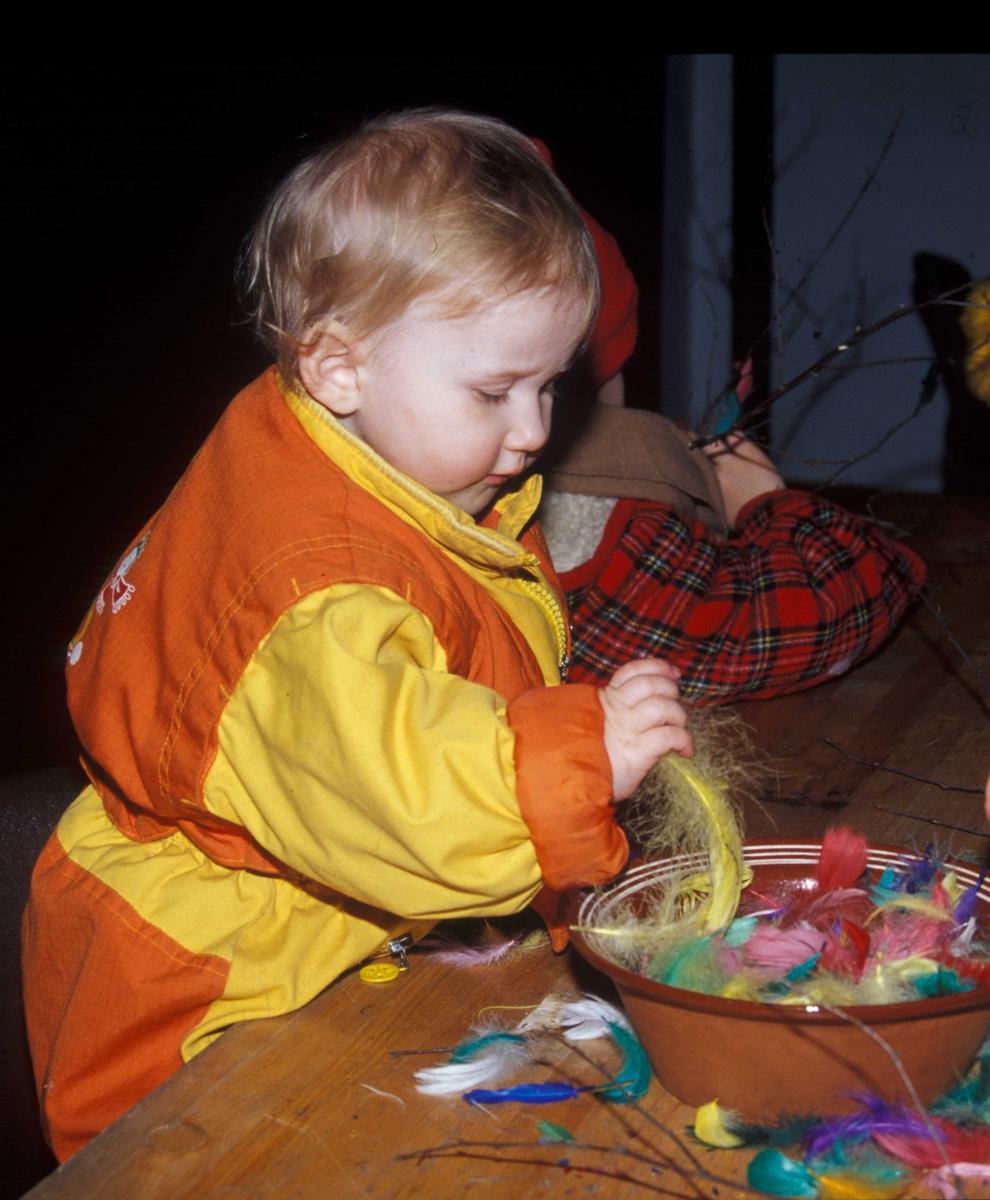 Feiring av fastelavn på Norsk Folkemuseum. Barna lager fastelavnsris i Hallen. Lite barn med en bolle full av fjær i fine farger.