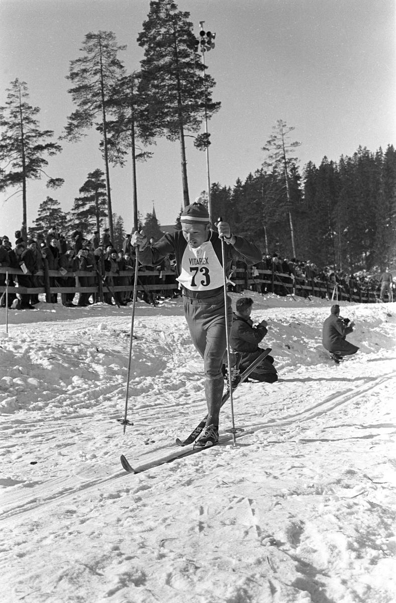 Skiløper med startnummer 73 i Holmenkollen. Publikum langs løypa.  Pressefotografer på sidelinjen. Holmenkollrennene 1963.