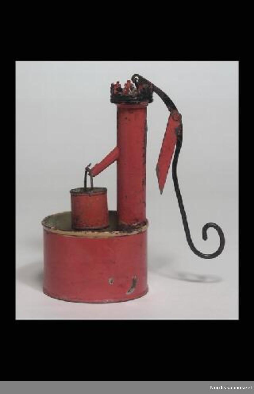 Inventering Sesam 1996-1999: H 16,3    Diameter 8,2  (cm) Vattenpump, leksak, av bleckplåt, rödlackerad. Högt smalt cylindriskt pumphus, upptill med kreneleringar, kran och s-formad pumparm, röd hink, cylindriskt kar. Pumparmens infästning med trasig lödfog. Birgitta Martinius 1997