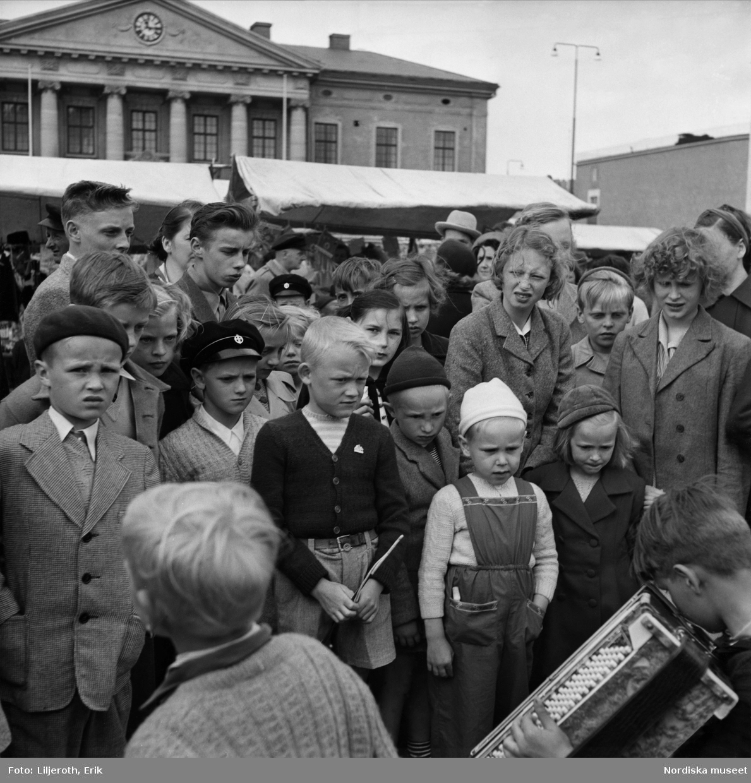 En samling ungdomar som lyssnar på en pojke som spelar dragspel