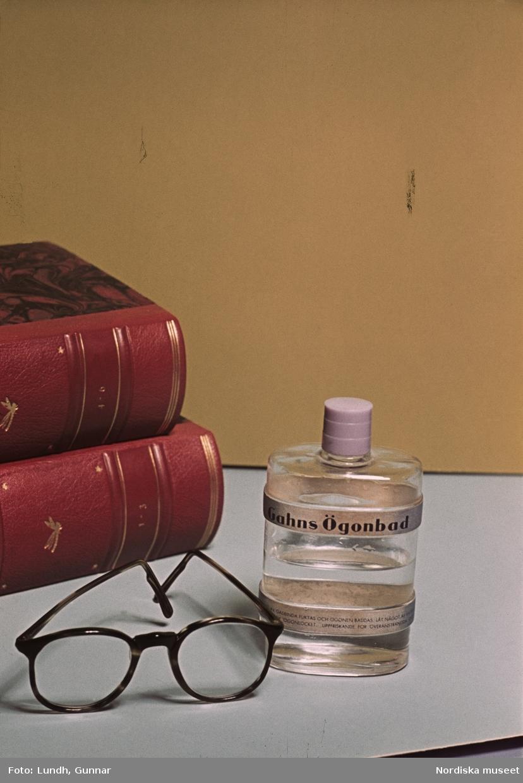 """Stilleben med böcker, glasögon och en flaska """"Gahns ögonbad""""."""