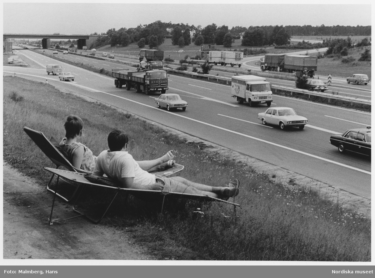 Autobahn, Västtyskland, 1972. Ett par i solstolar tittar på motorvägstrafik.