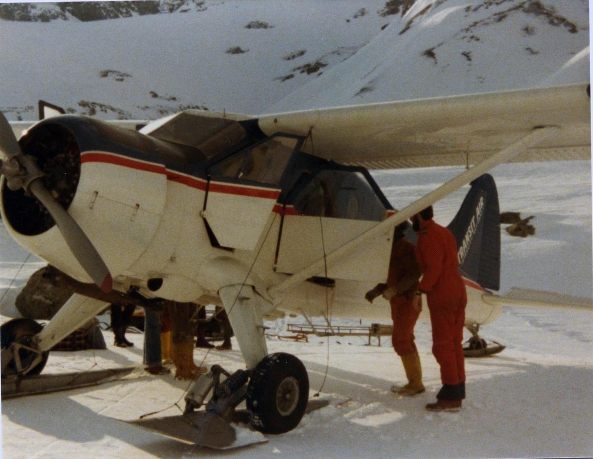 Landskap. Ett fly på bakken, LN-KCQ, DHC-2 Beaver. utstyrt med hjul og ski. Snøføre. Noen personer ved flyet