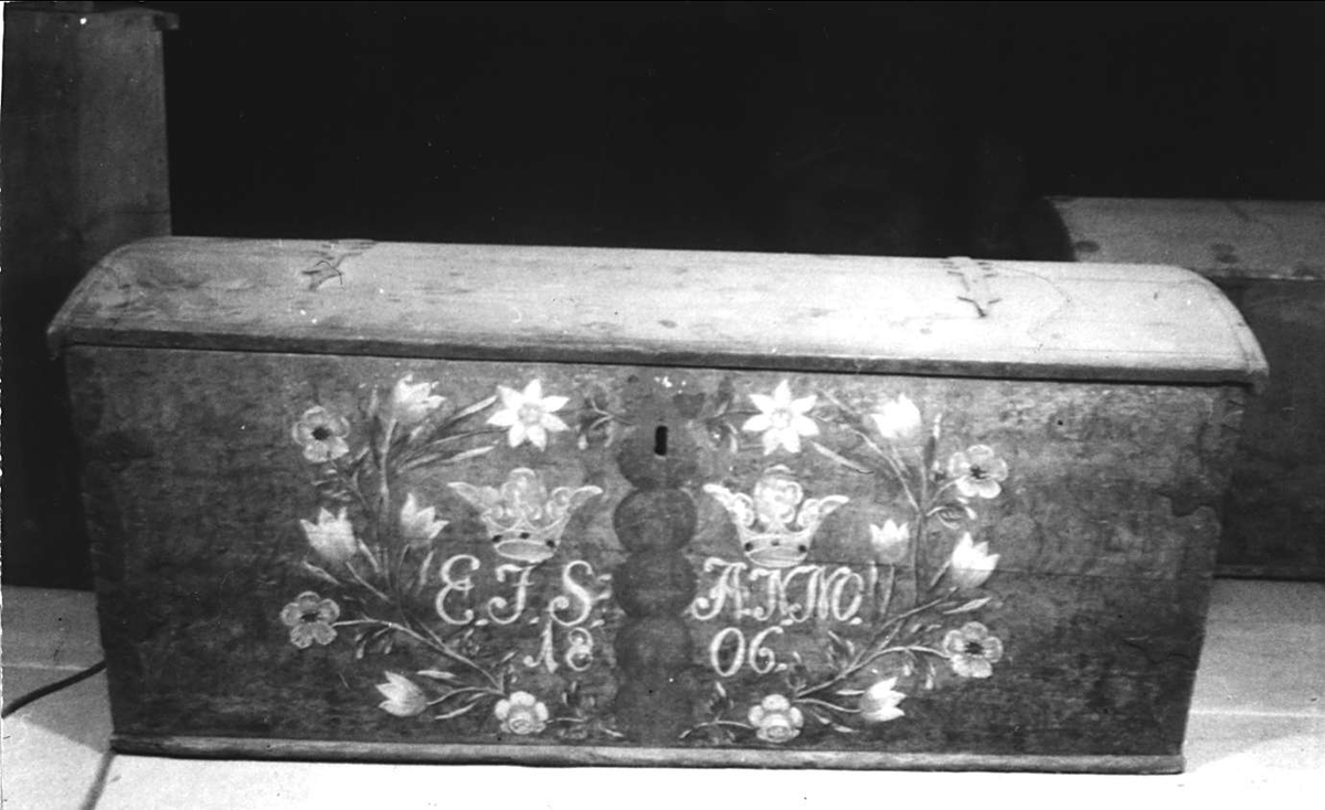 Kista av trä. Brunmarmorerad med rester av grön färg på locket. Grönmålade kanter och hörn. På locket en rödvit blomma och ett hjärta i varje hörn. På framsidan dekor i rött, vitt, gult och svart. Vit text: E J S ANNO 1806. Kista av trä. Imiterat mittbeslag målat i grönt. Handtag och beslag av järn. Läddika med lock. Låset ligger löst i läddikan.