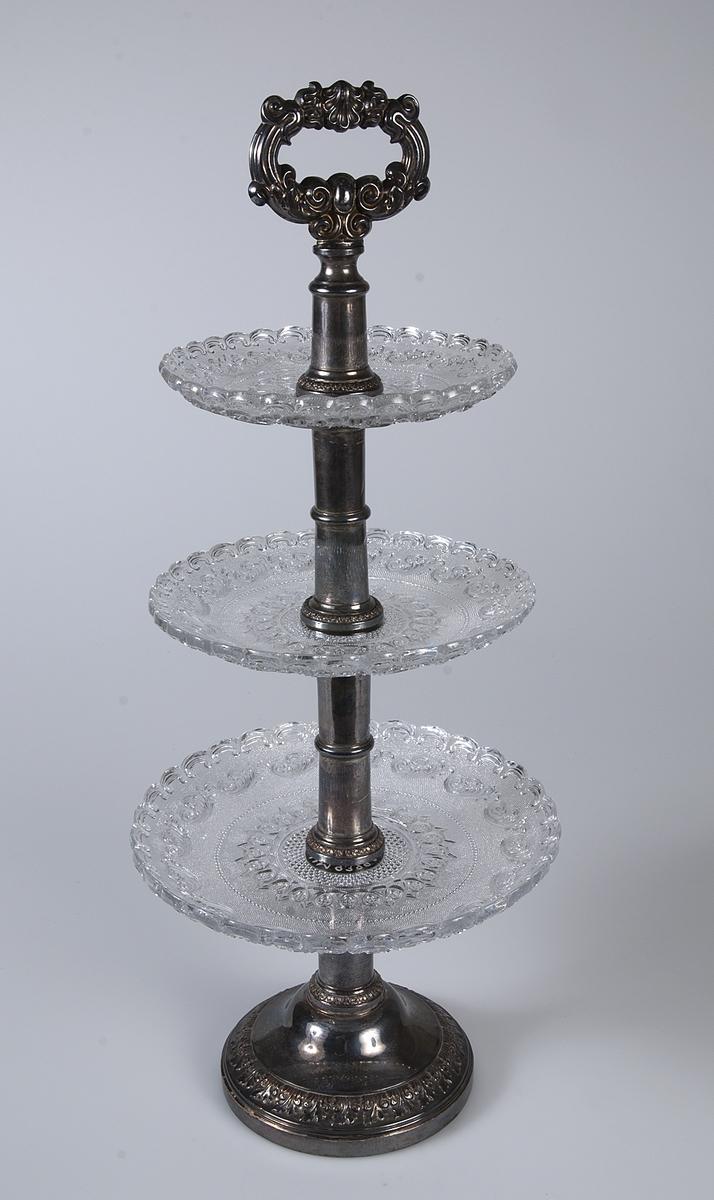 Kakfat, etager, med fot (UM09329a) av icke solitt silver med två otydliga stämplar samt tre tallrikar (UM09329b) av pressat glas. Från fotrundeln stiger en kraftig järnten på vilken tallrikarna omväxlande med fotens skaftdelar träs på. Till sist påskruvas handtaget.
