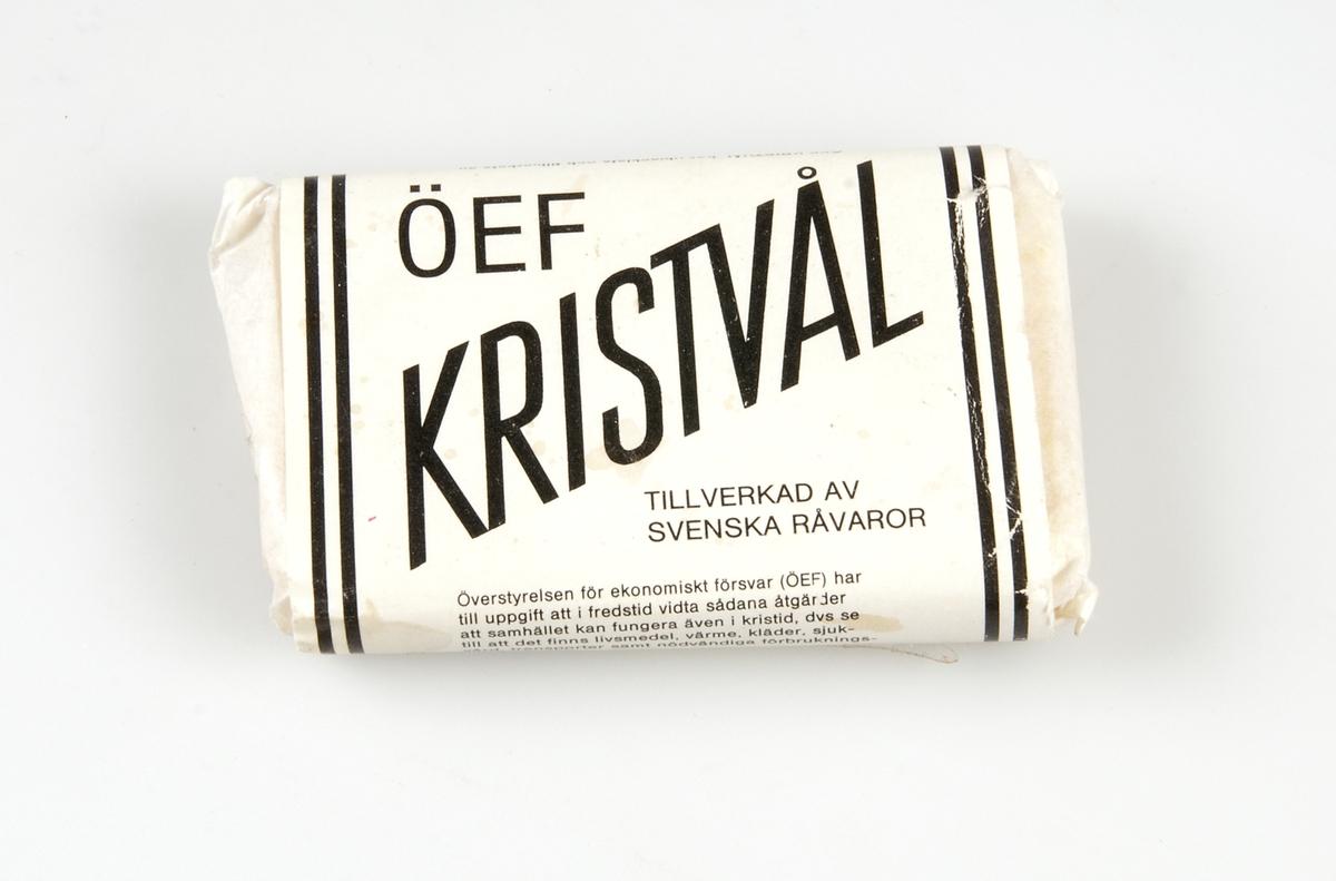 Förpackning av papper med liten tvål. Vitt papper med svart text: ÖEF KRISTVÅL. Av texten framgår att ÖEF är Överstyrelsen för ekonomiskt försvar.