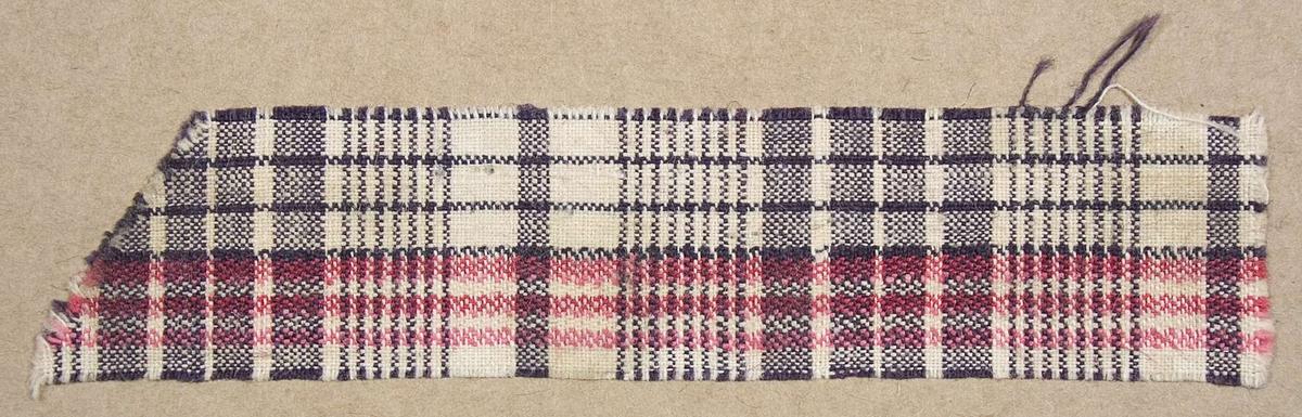 """Vävprov ämnat för klänningstyg vävt med bomullsgarn i tuskaft med korskypertränder. Rutmönstrad i färgerna vitt, rött och grått. Vävprovet är uppklistrat på en kartong i storleken 22 x 28 cm. I övre högra hörnet finns en stämpel """"Uppsala läns hemslöjdsförening"""" och ett handskrivet nummer, """"A.448."""""""