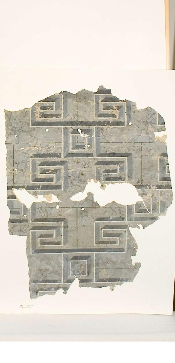 Tapetprov med tryckt mönster i grått och vitt. Stenimitation med labyrintmönster. Text på baksidan av kartongen: Nr 84 Kv. Svanhild nr 4 NV huset, 1 tr Rum 2.