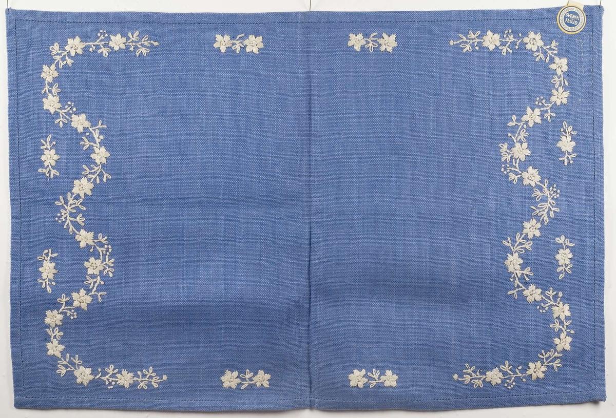 Broderad duk med blommotiv. Broderiet är utfört på blått linnetyg med vitt lingarn. Broderistygnen består av bland annat stjälkstygn och plattsöm. Broderiet är märkt B4058.