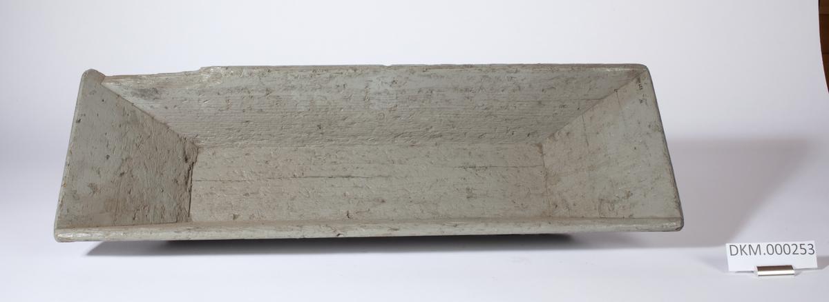 """Uvanlig form til trau å være. (Kartotekkort DKM 253).  Trauet er """"traktformet"""" på en side i den ene enden. Den uvanlige formen gjør trauet bedre egnet til å tømme/helle mynter, opp i for eksempel en pose."""