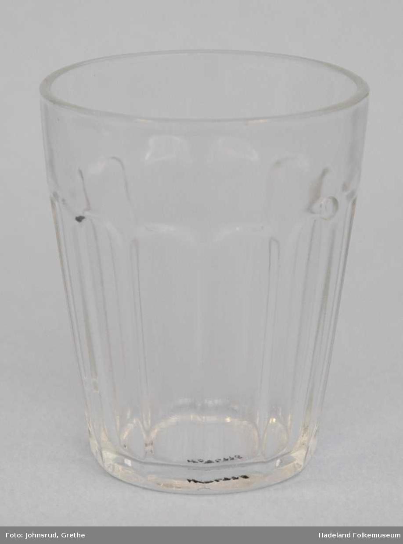 Gjennomsiktig, klart glass. 12 kantet, men rundt nede og ved åpning øverst. Luftbobler i glass. Noe opphøyd bunn.