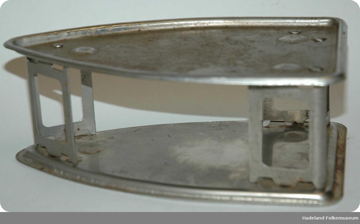 Til å sette varmt styrkejern på. Jern med rustfritt belegg. Av tynne plater, stanset ut. 2 like plater med avstivere imellom. Spiss foran, rett bak. Begge sider kan brukes opp. Til elektrisk strykejern.