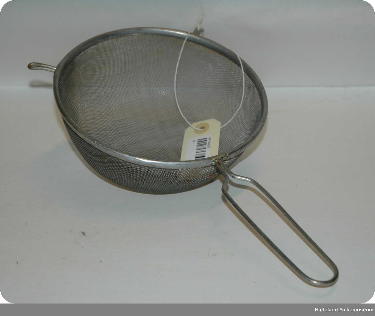 Silen er rund med metalltråder som danner mønster som tett netting. Metallkant rundt silen med håndtak av rund metalltråd formet som et rektangel med buet ende. På kanten av silen er to kroker / ører slik at silen kan ligge på kanten av kjele eller bolle.