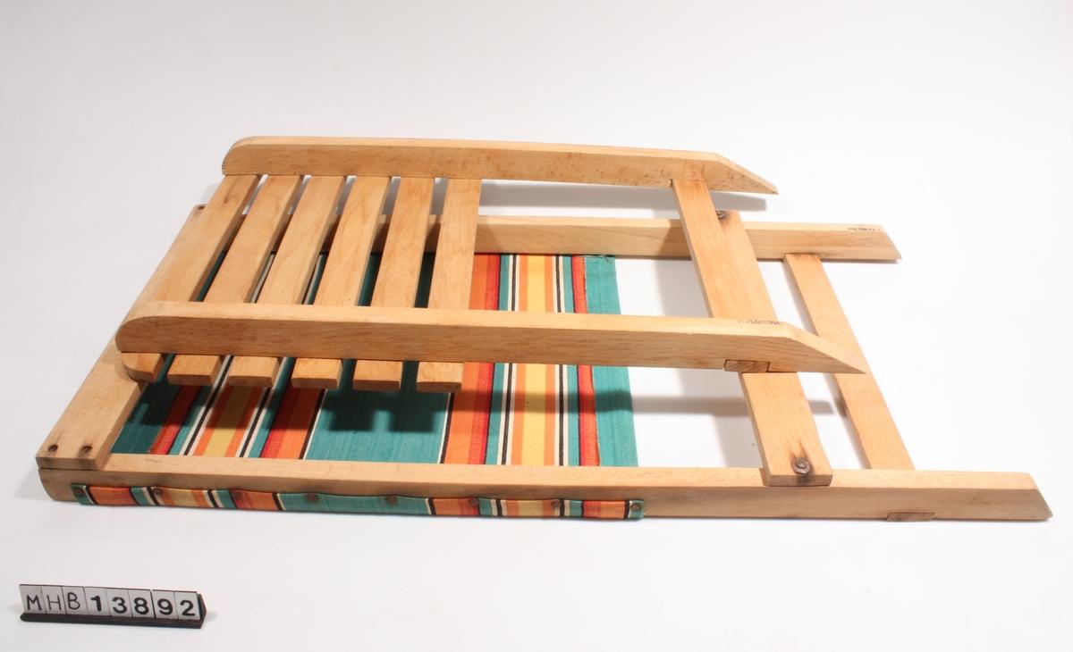 Strandstol i to deler; rygg og sete. Ryggen består av to stående planker, som oppe og to steder nede er forbundet med tversgående planker. Et stoffstykke er spent over og naglet fast til de stående plankene, slik at det danner ryggen på stolen. Setet består av to sideplanker som er skåret skrått nederst. Den ene halvdelen er dekket av 6 tversgående planker som danner selve setet. Setet kan føres inn gjennom de to nederste tversgående plankene i ryggen, slik at de to delene står vinkelrett på hverandre.