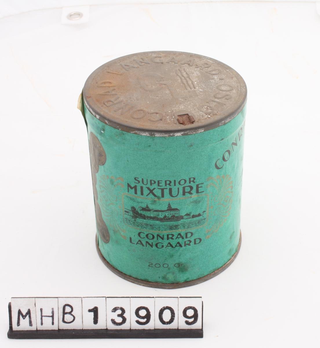 Sylinderformet tobakksboks av metall, med metallokk og papiretikette som i helhet dekker boksens stående sider.