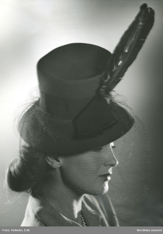 Porträtt av kvinna i hatt med fjäder, flor och hattband, från Madame Suzy.