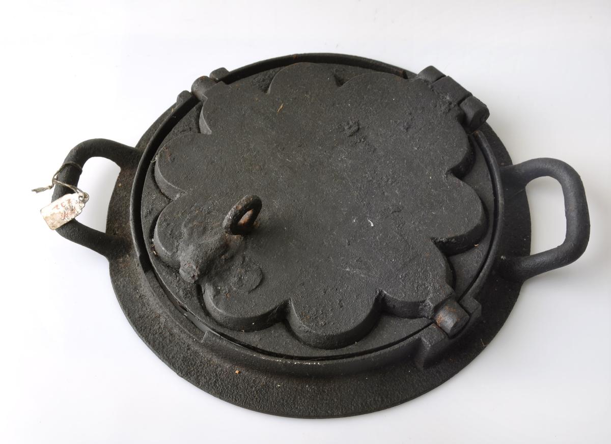 """Form: 5-hjerters jern. Både på toppen og bunnen er det en """"utvekst"""" med hull til å stikke en krok i for å åpne for å se om vaffelen er ferdig."""