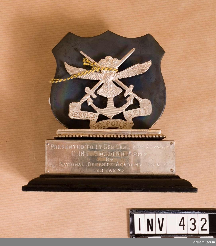 """Samhörande nr är 294-299, 321-350, 400-448. Minnestecken från kadettskolan, Poona, Indien. Emblem i silver på trä från indiska försvarets gemensamma kadettskola i Poona (Pune). Överlämnat 1795-01-23 under CA besök vid indiska armén jan 1975. (""""Presented to Lt Gen Carl Eric Almgren, C-in-C Swedish Army, by National Defence Academy, India, 23 Jan 1975."""")"""