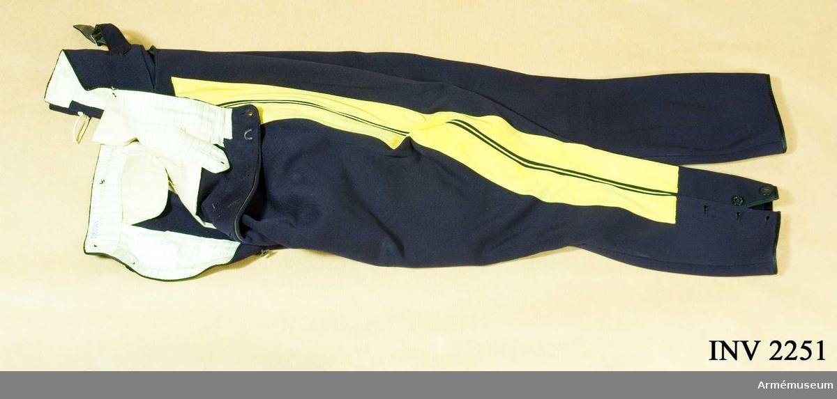 """Generalstab.Stl B 152. Av mörkblå yllediagonal med dubbla gula klädeslister  och mellan dem em gul passpoal (GO 30 jan 1845, nr 72).  Julpknäppt med fem svarta byxknappar varav en del märkta """"For Gentlemen"""", några """"Lundqvist"""" och en del """"MEA"""". Infodrat  med randat, vitt fodertyg. Två sidfickor fram, två bak. En klockficka på höger framstycke. Spänntamp mitt bak för reglering av byxans midjevidd. Litet sprund med hank för   upphängning. Skurna med vid tillskärning och på utsidan av vaden ett sprund med tre knappar märkta """"MEA"""", """"Janson"""" och """"Wallgren""""."""