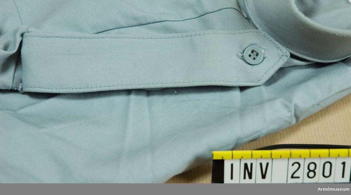 Dubbelvikt med smalare underdel. Knapphål på båda delarna för fastknäppning i den hälla som finns på skjortan. Fastsättning i ärmsömmen.