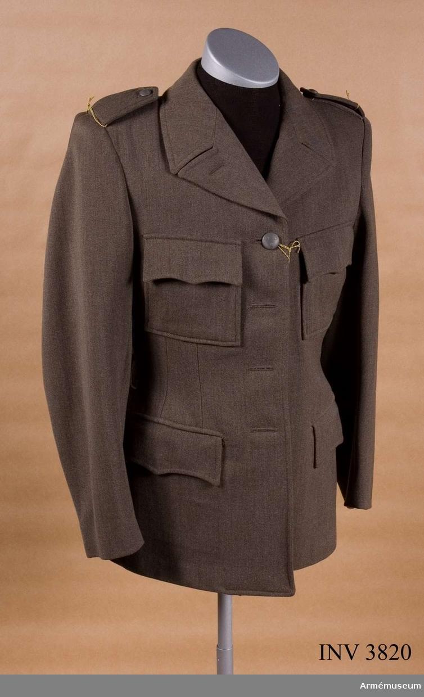 """Av gråbrungrön kommiss eller diagonal. Knäppt m fyra stora  knappar m/1939. Löstagbara axelklaffar. På var axel två  trådslejfar f fästande av axelklaff som knäppes m små knappar  m/1939. Nedvikt krage. Slag som kan bäras hop- eller uppknäppta  m liten knapp m/1939 på kragens undre V del. Sprund i ryggen och  två veck. I var sidsöm en hälla f skärp av samma tyg. Två  påsydda bröstfickor m bälg i sidorna. Spetsskurna lock. Helt  liv-/ärmfodrad m konstsiden, även ficklocken. Märkt """"40"""" på  livfodret i ryggen under hängaren. På V skörts insida """"ACB"""".Tjänstetecken: utföres i metall, knappar i bronsfärg,  tjänsteklassbeteckning i mörkblått. Utgöres av stjärnor,  stjärnknappar, stolpar och fyrkantsgalon, anlagda enligt  m/1939-systemet. På kragen truppslags- eller  personalkårstillhörighet. På axelklaffar förbandstillhörighet  och i förekommande fall tjänsteklassbeteckning. För personal ur  SLK, SBS, SRK och sjuksköterskor tjänstetecken m/1946,  stort/litet, i stället f truppsl.-/förbandstecken. Av metall m  vederbörlig organisations emblem. Lackerat eller i emalj."""