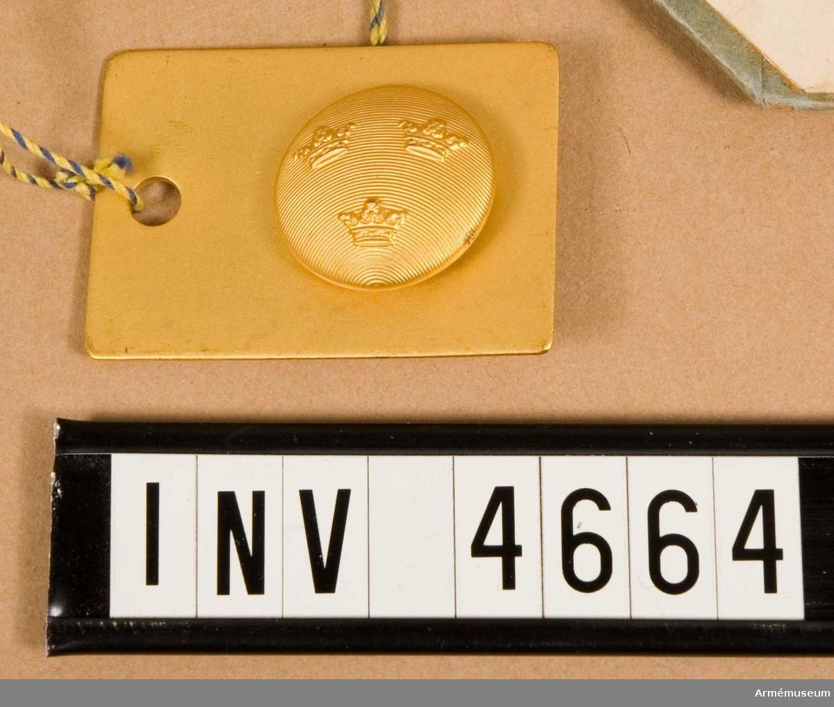 """Likaren är avsedd för emblem, knappar m fl tillbehör till  uniform m/1952. Färglikaren består av en platta av metall vars  färg är likare för färgen å tjänstetecken till uniform m/1952. Som exempel är en manskapsknapp - tre kronor - anbringad; den är benämnd Knapp m/1952 för övrig personal, stor. För fastsättning vid plattan är detta modellexemplar försett med två klammer på baksidan. Vidhängande etikett anger fastställelsedag: """"Stockholm Slott den 14/8 1952 Torsten Nilsson C. Årmann""""."""