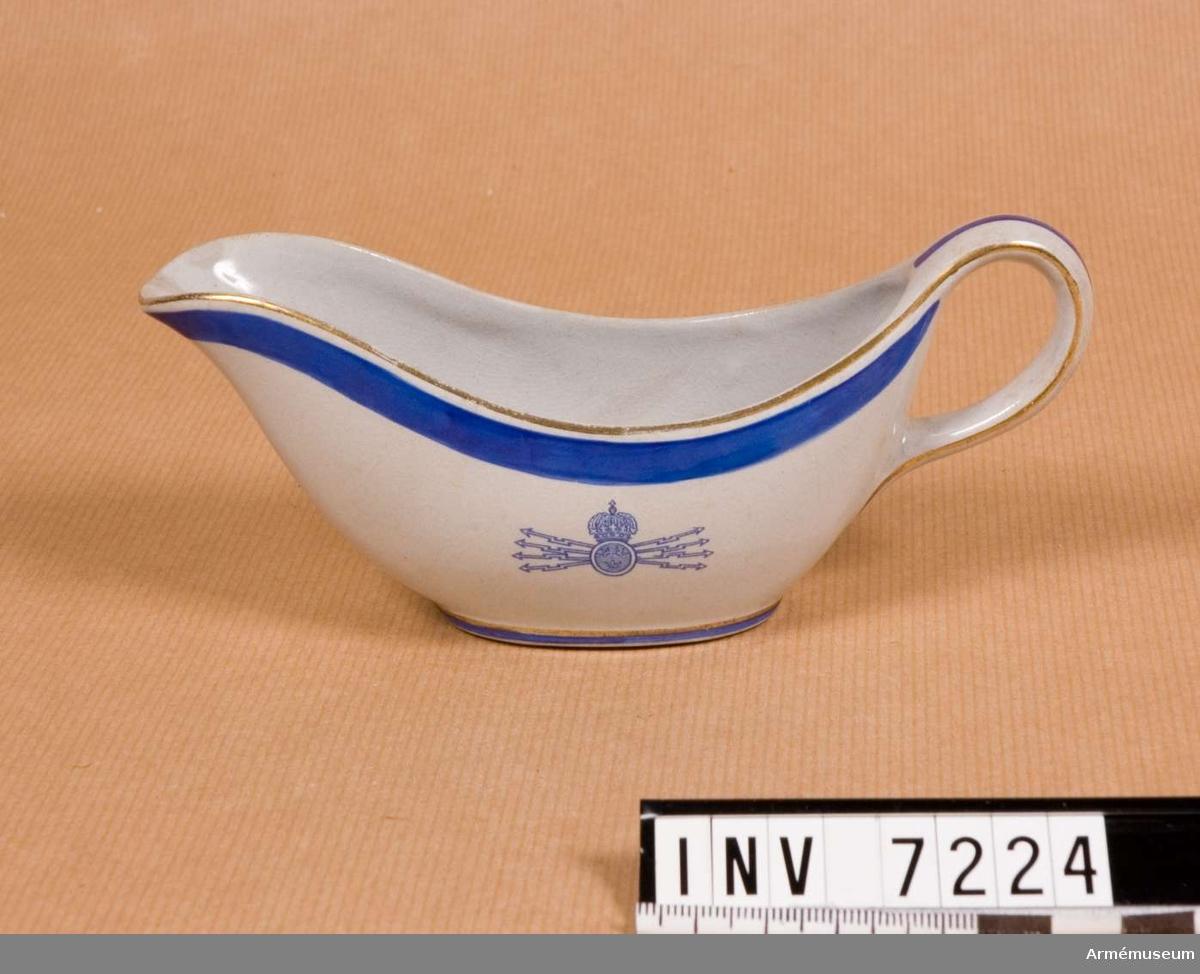 Samhörande nr är 7218-26, 7228-30 matporslin. I grått porslin med blå rand och guldkant samt med   Fälttelegrafkårens emblem på ena sidan.  Användes till smält smör eller möjligen grädde. Färg grå, blå, guld Q,L,D. Gott skick.
