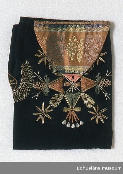 Handsydd halvvante av svart kläde, på ovansidan prydd med en trekant av mönstervävt sidentyg. Broderad med silketråd i ett glest broderi, med fjäderliknande former i bred kråkspark, stjärnliknande mönsterfigurer i raka stygn och en slinga i flätsöm vid tummen. Färgerna i sidentyget och broderiet är ljust röd- och gulbrunt, ljusgult, grönt samt aningen vitt, blått och svart. Snarlika vantar finns på sid. 13 i Notini 1980 (se litt. listan). Dessa kallas kyrkvantar för sommartid och hör till Delsbodräkten. Tillverkningstid och användningstid uppskattade.  Enligt text i gåvobok, i museets arkiv D:4B:1, är vanten inköpt av fru Rosa Jacobowsky 1904? på auktion efter fornsakssamlaren Johan Norder i Torp socken (Dalsland). Sliten, speciellt på tummen. Sidentyget sönder i trekantens spets.  Rosa Jacobowsky (1860-1954), gift med grosshandlare Efraim Jacobowsky, Uddevalla.  Ur handskrivna katalogen 1957-1958: Halvvante L. 15, Br. 12 cm; svart kläde  m. silkebroderier; på ovansid. en påsydd trekant av polykromt silke, broderad. Hel.  Lappkatalog: 78 Litt; Notini, Anja, Dräktfolket Möte med tradition, Stockholm 1980. Nylén, Anna-Maja, Folkdräkter ur Nordiska museets samlingar Nordiska museets handlingar 77, Lund 1971, sid. 67-70.  Widhja, Inger, Takhimlar och brudhandskar Folklig textiltradition i Västergötland, Skara 1990, sid 132-133.  Omkatalogiserat 1997-03-24 VBT