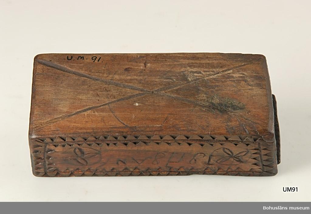"""Rektangulär låda med skjutlock och något snedställda kortsidor. Skuren dekor bestående av rosetter, kors samt uddsnitt längs kanterna. På en av långsidorna är årtalet """"1848"""" och initialerna """"AN"""" inskurna. Inuti ligger en äldre etikett från ca sekelskiftet. Kan vara en friargåva.  Litteratur: Gjaerder, Per, Esker og tiner, C. Huitfeldts förlag, Oslo, 1981, s. 41. Knutsson, Johan, Friargåvor, Nordiska museets förlag, Stockholm, 1996.  Ur handskrivna katalogen 1957-1958: """"Trälåda 1870-1887 Bottenmått: 14 x 5,5 H. 5. Trä med skuren ornering. Föremålet helt. Bohusl.""""  Lappkatalog: 84"""