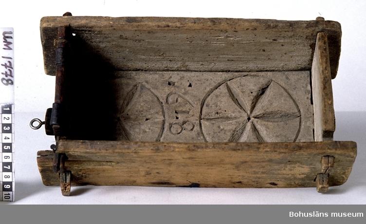 """Rektangulär ostform med fyra gavlar ihopfogade med tappar och sprintar. Lös botten med två rosetter i karvsnitt och årtalet """":1819:"""" inskuret. Fem avrinningshål. Har kvar fragment av grå färg? på utsidan. Sekundärt lagad med två järnband på en av kortsidorna. En av långsidorna har varit rejält angripen av skadedjur och är trasig. Litt; Ränk, Gustav, """"Från mjölk till ost"""", Berlingska boktryckeriet, Lund 1966. Omkatalogiserat 1996-05-21 AN  Ur handskrivna katalogen 1957-1958: Ostform, fyrkantig, Forshälla. Mått: 32 x 18 x 11 cm. bottenbrädan mönstr. och har 5 genomg. hål, jämte: """":1819:""""; fogad m. tappar och sprintar; Trasig, lagad m. järnband.  Lappkatalog: 53"""