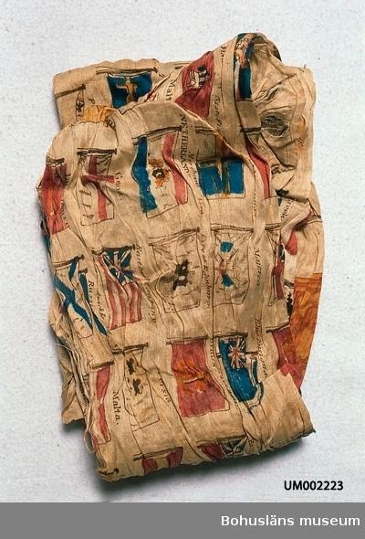 """Silketyg med tryckt mönster av olika flaggor (nations-, stads- och handelsföretagsflaggor mm?). Färgerna är nu beige botten och tryck i mörkbrunt, blått, blåtonat rött, gråtonat gult. På ett ställe texten: """"Greek: 1829"""". Datering gjord efter det. Bredvid duken ligger två etiketter: """"Duk med flaggor Gåva av Simmersröd Barnhus U (?) Överstelöjt Hjortsberg"""" och """" Gåfva af Skräddaremästare Gylb... (oläsligt) i Resteröd 1880"""". Årtalet 1880 är möljligen det år då Simmersröd Barnhus fått duken. I mycket dåligt skick. Bitvis helt söndertrasad. Troligen färgförändrad. Går ej att lägga ut för mätning, trasas då sönder.  Ur handskrivna katalogen 1957-1958: Sidenduk m. flaggor Mått: 85 x c:a 65 cm. vitt (?) siden m. flaggor i färgtryck. Mycket trasig. Simmersröd, Ljungskile."""