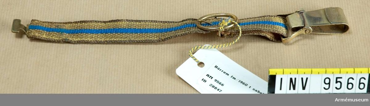 Tillverkat av gult och blått silke och med karbinhake för remmens fästande i sabeln. Foder av naturellt skinn. Gåva från FMV.