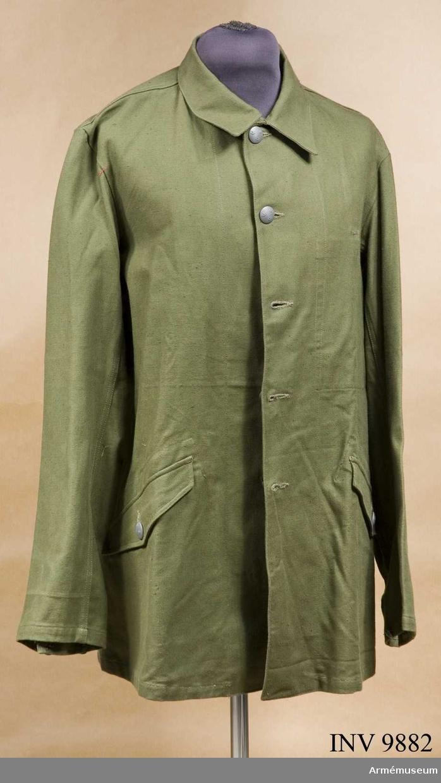 Storlek 50 C. Tillverkad i grönt bomullstyg med knäppning fram med grå kronknappar. Har två sidfickor med lock.