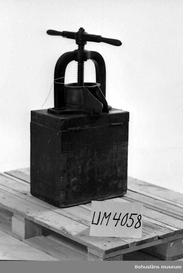 """Ur handskrivna katalogen 1957-1958: Skålpress f. bl. a. tinkturkryddor. H. (nedskruvad) 80 cm; en kraftig sockel av trä, som en låda, på vars """"lock"""" pressen är fäst; en skål av mässing m. pip; en kraftig arm, L. 34,5 cm, att vrida; i en bygel av järn; """"locket"""" är på gångjärn och genom att lyfta detta rinner det presssade ut. Järnet rostigt. Ett gångjärn trasigt.  Lappkatalog: 94"""