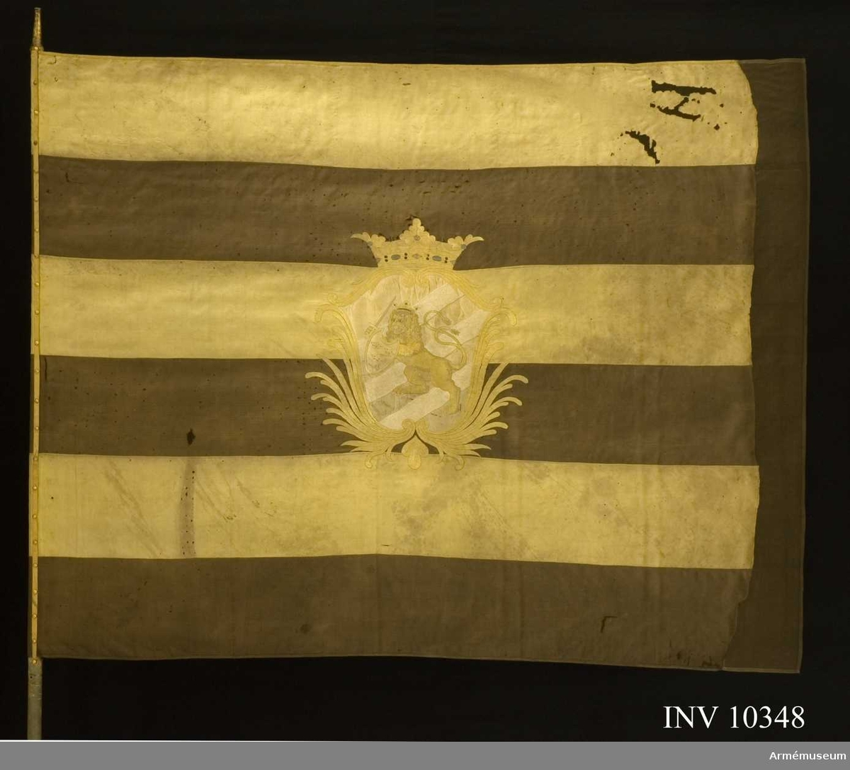 """Grupp B I.  Duk av sidenkypert, fem gånger delad gul och svart, i mitten broderat Göteborgs vapen; 1812-1819. På blått fält tre vita strömmar snett från vänster varöver ett framåtvänt krönt lejon i gult silke förande ett svärd och en sköld vari """"tre kronor"""" på blått fält allt i en av stiliserade palmkvistar i gult silke bildad sköld, krönt med öppen krona i gult silke med rött foder samt pärlor i silver, kantad med gult sidenband, fäst med liknande sidenband och förgyllda spikar. Spets saknas."""