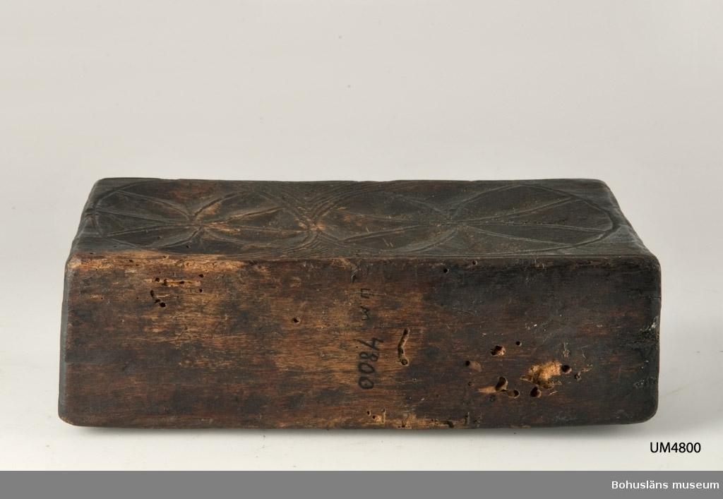 """""""Bokformad"""" låda vilken saknar skjutlock på långsidan. Dekor bestående av rosetter. Betsad eller tjärad? Något defekt samt skadedjursangrepp.  Litteratur: Gjaerder, Per, Esker og tiner, C. Huitfeldts förlag, Oslo, 1981, s. 53-55.  Ur handskrivna katalogen 1957-1958: Bokfodral i helt trä Bottenmått 21 x 6,5 H. 12,5 Av trä med karvsnitt. Utan lock. Svart. Föremålet helt. Maskhål.  Lappkatalog: 68"""