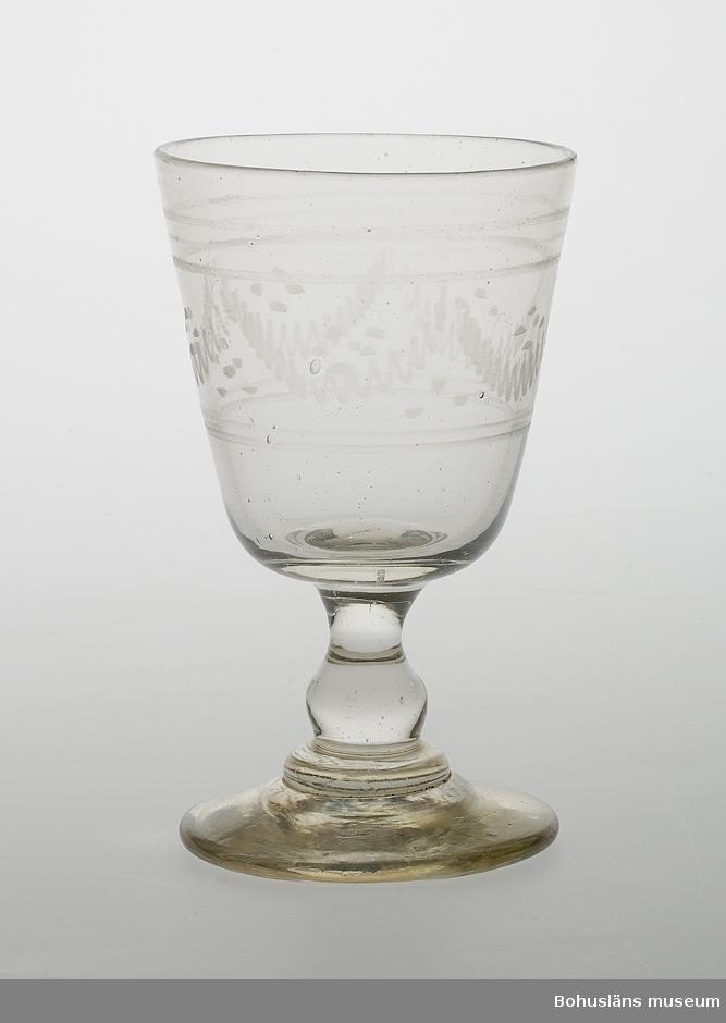 Ur handskrivna katalogen 1957-1958: Ölglas, handetsat Mynningsdiam.: 8,2. H: 13,8. Skål med vit dekor, lågt skaft, rund fot. Hel.