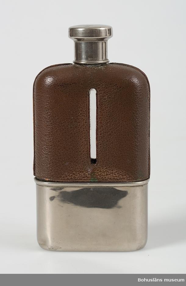 """Platt glasflaska med kort hals. Ett skyddshölje av brunt läder kring flaskkroppen med en smal öppning för avläsning av nivå, nertill skyddsskoning av blank plåt. Skruvkork av plåt, märkt """"GERMANY""""."""
