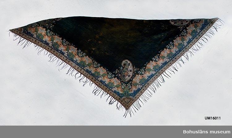 """Trekantig (delad) svart schal med varp av silke och inslag av ull, med mönstervävd bård. Den 19 cm breda bården har ett detaljrikt orientaliskt mönster med koraller, blad och små blommor, med svart bottenfärg och svarta konturer kring mönstren i ljusbrunt, grönt, blått, beige och vitt. Mitt på sidorna är bården spegelvänd. Diagonalen handfållad. De två andra sidorna har påknutna fransar av svart, glansigt ullgarn. Motivet i hörnet, innanför bården, är mir-i-botha-motiv, i Sverige ibland kallat """"schalgurka"""", """"flamman"""" med mera (se litteraturlistan Sandberg). Paisleyschalar, som schalar av denna typ kallas även om de inte alltid är gjorda i Paisley (Skottland), har ofta mir-i-botha-motiv. Därför har det med tiden även kommit att kallas """"paisley-mönster"""". Schalar av Paisleytyp försöker efterlikna orientaliska cashmereschalar. Troligen handvävd i vävstol med harneskrustning. Mönstret har kantigare former än de man med säkerhet kan säga är gjorda i jacquardvävstol ( UM004673, UM022926, UM023594, UM026245, UM026247, UM025127). I Paisley ökade antalet jacquardvävstolar först efter 1840. Enligt första katalogiseringen på museet: """"Tvåhundraårig äkta orientalisk schal"""". Om den uppgiften kommer från en gammal etikett på föremålet eller gäller vid inskrivningstillfället 1981 är oklart. Enligt anteckningar gjorda i samband med Gulli Klebergs gåva ingick i donationen en 200-årig äkta schal som var en gåva till Hemslöjdsföreningen från fru Hulda Hermansson, Grindhult, Bäfve socken, Lane Härad. Den schalen, som med all sannolikhet är UM016011, har tillhört """"fru Hermanssons farmors, farmors, farmor: Rådman Palmgrens fru Margareta i Marstrand"""". Möjligen kan schalen vara från 1700-talet. Datering har dock gjorts utifrån uppgifter hämtade ur litteraturen om material, format och vävteknik. För ytterligare uppgifter om givaren se UM016001 Småhål, några lagade. Bristning intill bården i ena hörnet. Mycket fläckig eller fläckvis blekt till brun färg."""