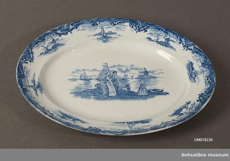 Tryckt blå dekor med hamn & och sjömotiv på spegeln (holländskt) och kvarnar samt båtar på brämet. Dekor: Hague, från 1900-talets första årtionden.