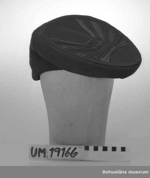 471 Tillverkningstid 1940-TAL 394 Landskap BOHUSLÄN  Damhatt i tunt svart tyg med taftfoder. Modell med längre bakparti än fram.  Rund platta upptill med lagda veck i omväxlande glansigt och matt tyg.   Se UM19130.