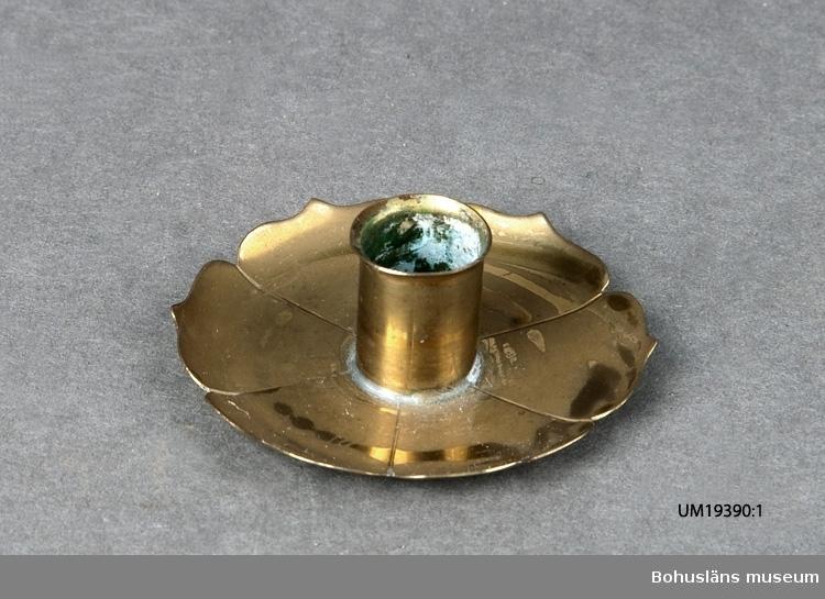 Liten ljusstake med hållare i mitten av en manschett/blad, den ena i ett par. För julgransljus.