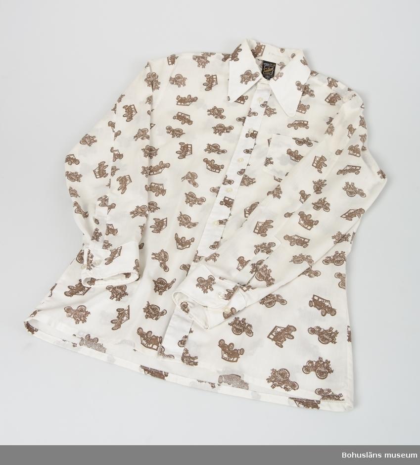 Mått ärmlängd 53 cm; kraghöjd 4 cm. Skjorta i bomull/polyester med bruna bilar tryckt på tyget. Stor krage och en bröstficka. Se UM019761.