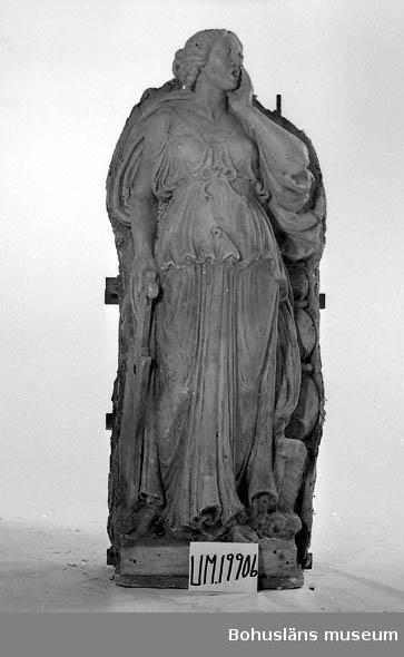 """Gipsförlaga till skulptur föreställande stående kvinna """"Gudinna"""" som sjunger eller ropar. Klädd, i lång tunn och veckrik dräkt och hållande ett instrument? i höger hand. Står på en 12 cm hög sockel. Statyns överdel vitgrå och den nedre delen gulbrun. Uppbyggd på en stomme av trä och fylld ett stråmaterial samt juteväv. På skulpturens sockel står det """"J.A. Wetterlund 1922"""". Dnr. 20-967/80. Där står antecknat: Ca 30 st gipsfigurer och verktyg som gåva till BM. Se även UM19236 -19250.  Förlaga till skulptur/allegorisk figur i granit placerade i runda nischer på byggnaden Göta källare, Hotellplatsen, Göteborg. Utförda 1922. Fyra olika skulpturer finns varav vtvå av förlagorna ingår i denna gåva.  Konstnären har gjort förlagan till lejonen i brons framför universitetsbyggnaden vid Vasaplatsen, Göteborg.  Litteratur: Se Svenskt konstnärslexikon del V för att få ytterligare upplysningar om hans verk. I Västgötagenealogen 1992:4 finns artikeln """"Johan Axel Wetterlund - slottsskulptören från Västergötland"""", Stieg-Erland Dagman, Habo."""