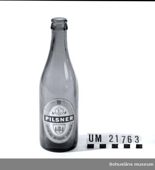 """Föremålet visas i basutställningen Uddevalla genom tiderna, Bohusläns museum, Uddevalla.  Grönfärgat glas. Märkt på etiketten med texten: """"Pilsner Utsiktens Bryggeri Uddevalla. II"""". År 1949 ändrades den bruna färgen i flaskorna till grönt. Utsiktens Bryggeri grundades 1854 på Underås, Uddevalla men på platsen hade funnits ett bränneri sedan 1820-talet.. Bryggeriet köptes 1919 av Pripp & Lyckholms. Utsiktens bryggeri lades ner 1961.   Flaskan är tillverkad av Årnäs glasbruk, Forshems sn, Västergötland.  Litteratur: Olsson, Hugo: Uddevalla förr. En bildbok. sid 138.  Från Internetkällan Uddevallabloggen är följande historik om Utsiktens bryggeri hämtad, skriven av Gunnar Klasson, Uddevalla: """"Idag [år 2007] finns det inga bryggerier i Uddevalla men annat var det förr. Ett av de äldsta var Utsiktens bryggeri från 1854 tätt följt av Svante Natt och Dags bryggeri i kvarteret Dagson. Natt och Dags bryggeri var länge det största som moderniserades och byggdes ut 1902. Men 1924 var konkursen ett faktum och bryggeriet lades ned. Samma år köpte Schwartzman & Nordström AB bryggeribyggnaderna och byggde om dem till konfektionsfabriken. Utsiktens bryggeri låg mellan Underåsgatan och Vintergatan på Väster. Bryggeriet fick sitt namn efter platsen som sedan länge kallades för Utsikten. På den tiden fanns det ingen bebyggelse utan då man stod på höjderna vid Annegreteberg (nuvarande Uddevalla sjukhusområde) hade man en strålande utsikt ut mot Byfjorden. På platsen låg i vart fall sedan 1830-talet ett brännvinsbränneri. Innehavare var den kände  Uddevallabon C A Kullgren, han med stenindustrin.  Kullgren avled på världsutställningen i London 1851 och hela bränneribranschen var vid den här tiden i gungning. De flesta småbrännerierna runt om i Sverige lades ned och produktionen koncentrerades till större enheter. Utsiktens brännvinsbränneri konverterades därför 1854 till ett ölbryggeri. På en del håll sågs detta till och med som en nykterhetsbefrämjande åtgärd. I början hette det Uddeva"""