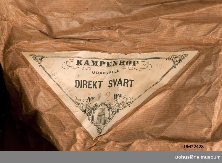 """594 Landskap BOHUSLÄN  Spånkorg med nystan av mattvarp. 10 svarta och 2 mörkblå nystan samt en garndocka i svart. Ett brunt omslagspapper med trekanting pappersetikett med tryckt text: """"KAMPENHOF UDDEVALLA DIREKT SVART No 12 Wa"""" täcker garnerna. På etiketten är det stämplat: """"13/6 1940"""". På papperet stämplat """"9 12 D"""". Troligen kommer mattvarpen ursprungligen från Kampenhofs bomullsspinneri. Papperets storlek: ca 87 x 57 cm.  UMFF 119:12"""