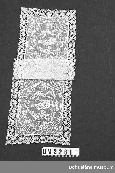 594 Landskap BOHUSLÄN  Tre st.likadana mönstergrupper bestående av två st.män och en kvinna. Rektangulär maskinvävd spetsmönstrad duk kantad med maskintillverkad spets. Lagad i ena hörnet med vit tråd.  UMFF 123:7